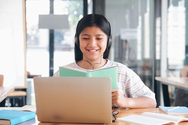 Enfant joyeux excité à l'aide d'un ordinateur pour l'apprentissage en ligne. éducation en ligne et concept d'auto-apprentissage et d'enseignement à la maison.