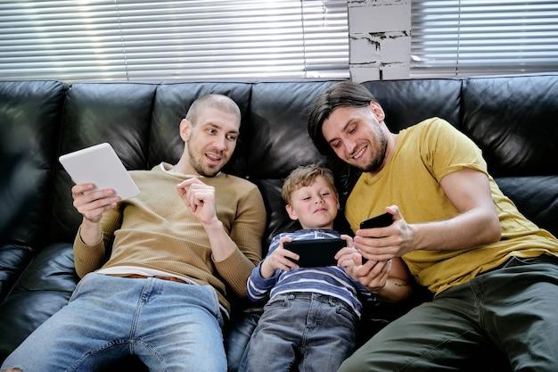 Un enfant joyeux et ses deux pères passent du temps ensemble, ils sont assis sur un canapé et jouent à des jeux sur des appareils mobiles