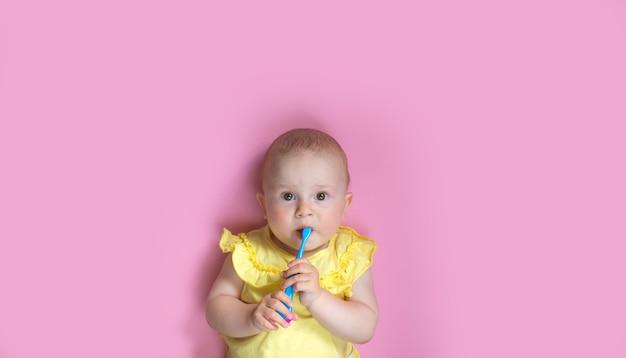 Enfant kid girl se brosser les dents sur fond rose. concept de soins de santé, d'hygiène dentaire, de personnes et de beauté. maquette, espace libre.