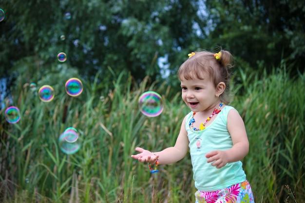 Enfant laisser les bulles de savon. mise au point sélective.