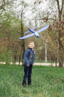 Un enfant lance un avion bleu dans la forêt