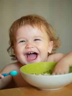 L'enfant de lancement mange un bébé souriant qui mange de la nourriture de la nourriture de la famille un enfant qui mange et le concept de parentalité