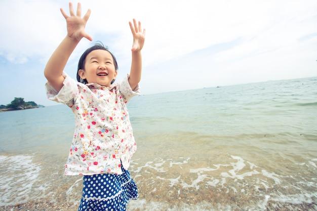 Un enfant lève la main au ciel sur la mer. je vois un sourire heureux.