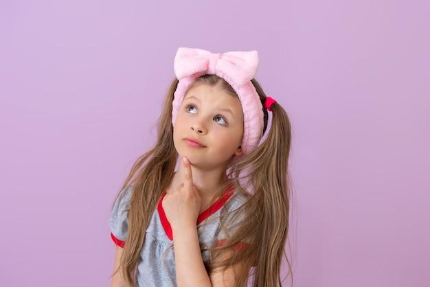 L'enfant lève les yeux d'un air pensif, soutenant sa tête avec sa main.