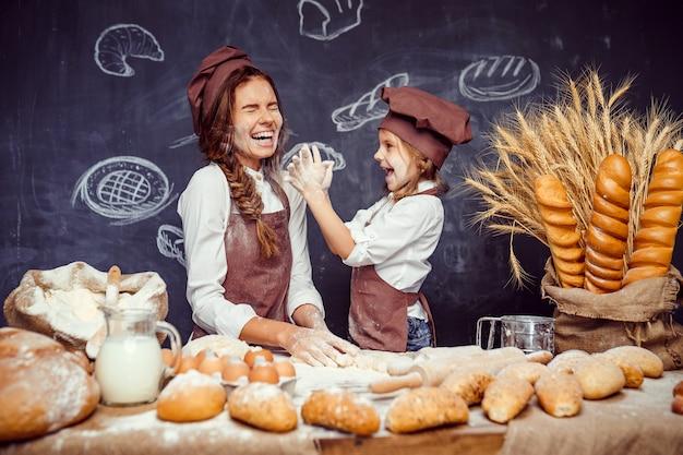 Enfant ludique avec mère faisant la pâte