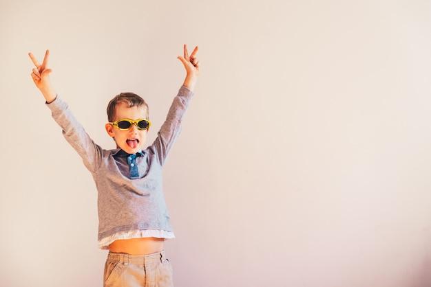 Enfant avec des lunettes de soleil drôles, levant les bras excités dans le signe de la victoire.