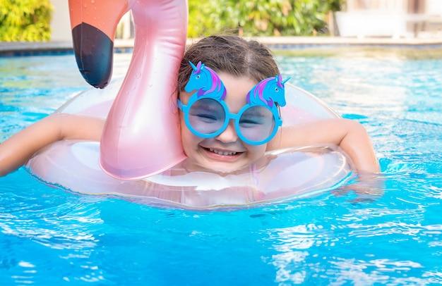 Un enfant en lunettes de soleil nage dans la piscine. fille s'amusant dans le cercle de natation