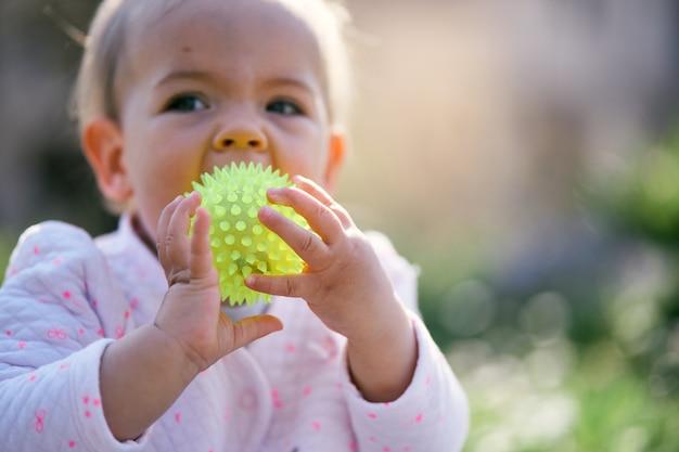 L'enfant mâche une balle en la tenant avec ses mains sur la pelouse