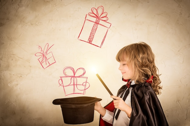 Enfant magicien tenant un chapeau haut de forme avec des coffrets cadeaux dessinés. concept de vacances de noël