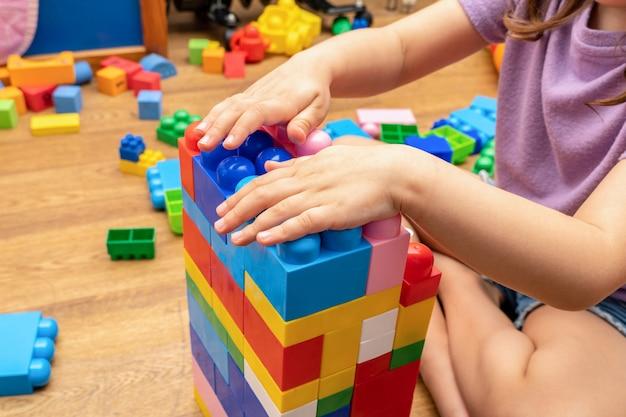 Enfant, mains d'enfant, tout en jouant avec le constructeur de blocs de jouets éducatifs