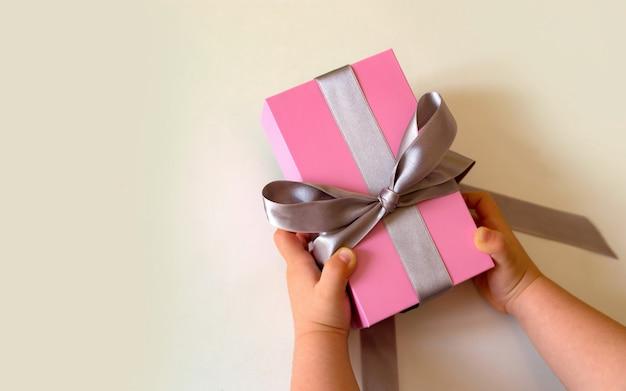 Enfant mains tenant une boîte cadeau rose avec un arc en argent