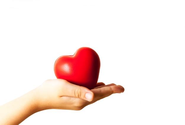 Enfant mains tenant coeur rouge, soins de santé, don et concept d'assurance famille