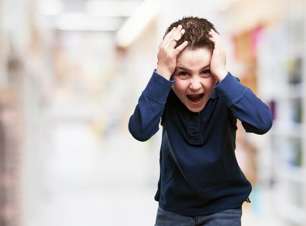 Enfant avec les mains sur la tête