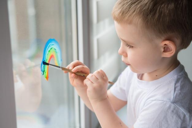Enfant à la maison dessine un arc-en-ciel sur la fenêtre