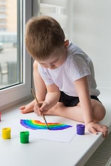 Enfant à la maison dessine un arc-en-ciel sur la feuille de papier