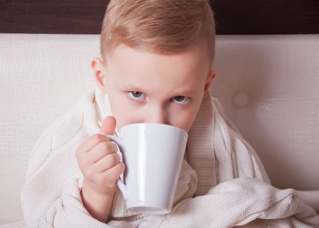 L'enfant malade assis dans un lit et tient une tasse de thé. concept de médecine.