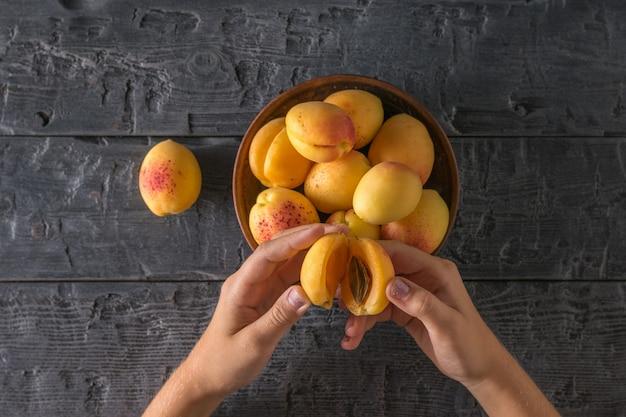 L'enfant mange des abricots mûrs d'une tasse d'argile sur une table en bois