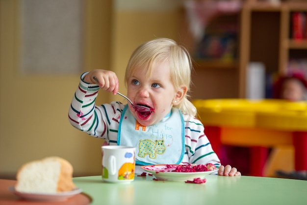 L'enfant mange des aliments sains à la maternelle ou à la maison et se salit