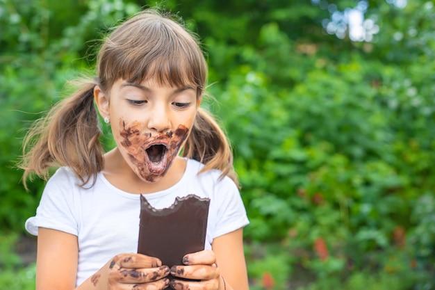 L'enfant mange une barre de chocolat.