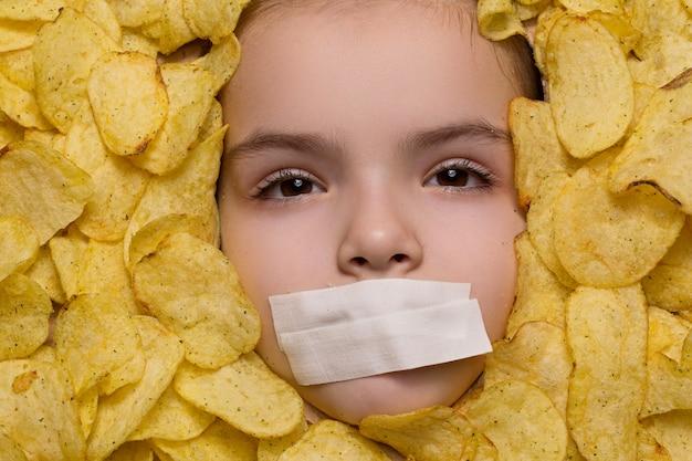 L'enfant mange des chips et c'est de la mauvaise nourriture