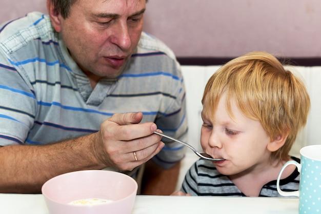 L'enfant mange avec la cuillère que tient le grand-père