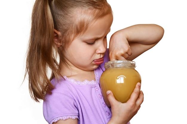 L'enfant mange du miel à la main dans un pot