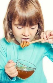 L'enfant mange du miel. mise au point sélective. la nature