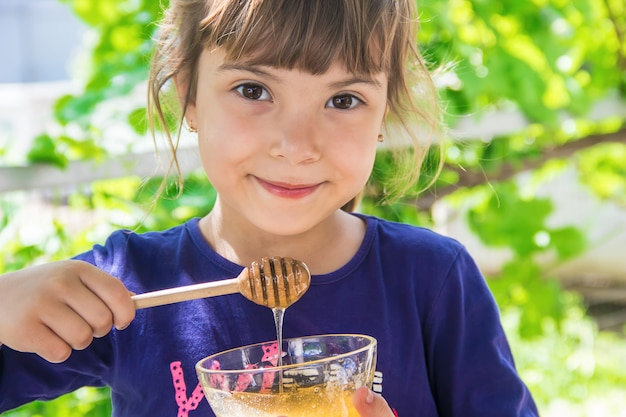 L'enfant mange du miel. mise au point sélective. la nature.