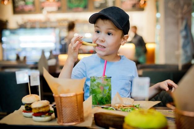 Un enfant mange fast food