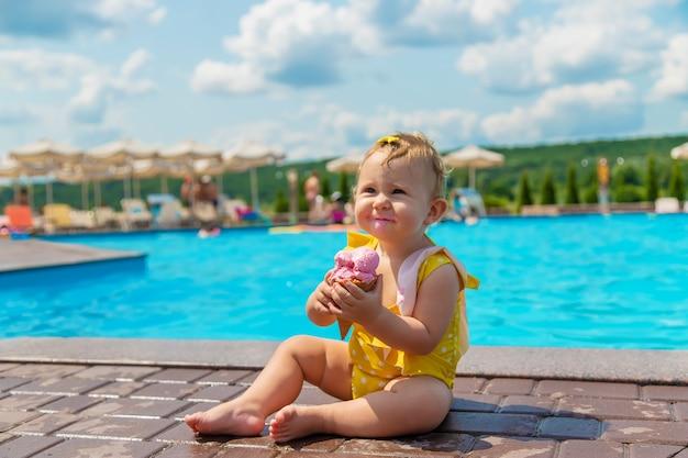 L'enfant mange une glace près de la piscine. mise au point sélective. enfant.