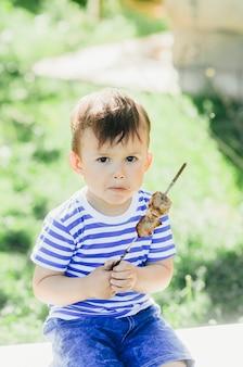 Un enfant mange un kebab sur une brochette, dans un parc ou une forêt nature fond vert d'arbres et d'herbe
