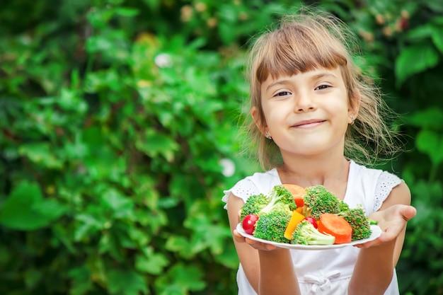 L'enfant mange des légumes. photo d'été. mise au point sélective.