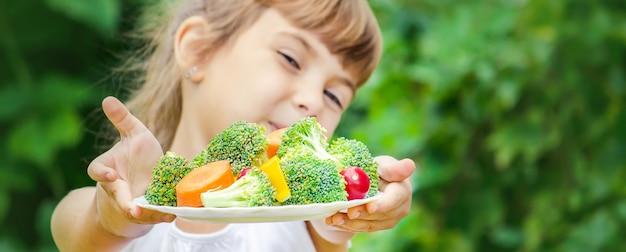 L'enfant mange des légumes. photo d'été. mise au point sélective