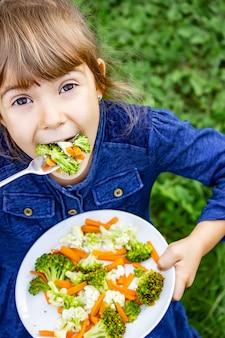 Enfant mange des légumes