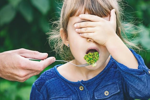 L'enfant mange des légumes.