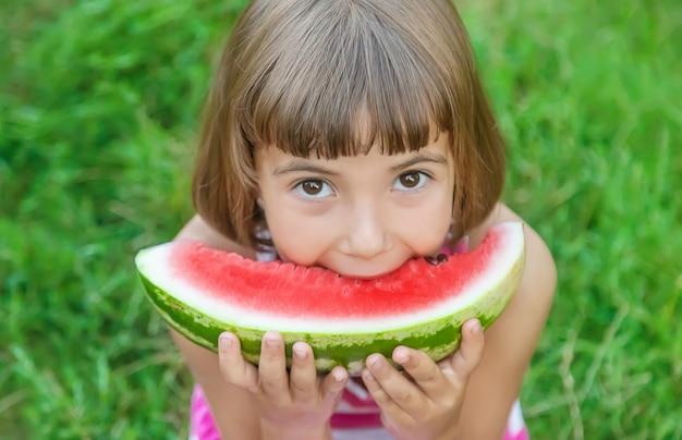 Enfant mange une pastèque dans le jardin