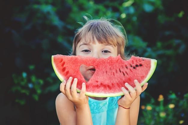 L'enfant mange de la pastèque en été. mise au point sélective.