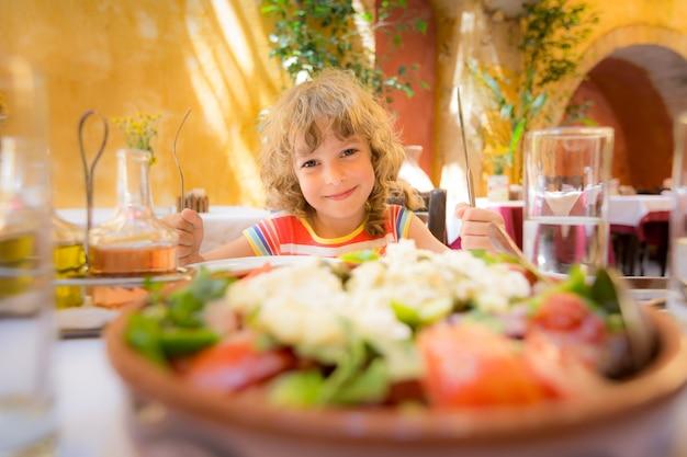 Enfant mangeant au café d'été à l'extérieur