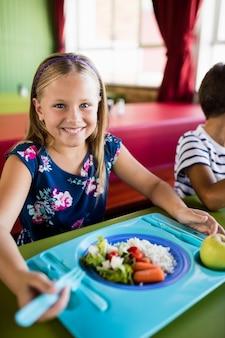 Enfant mangeant à la cantine