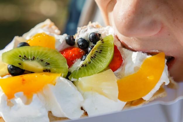 Enfant mangeant un gâteau gaufré frais avec des fruits et de la crème fouettée en vacances.