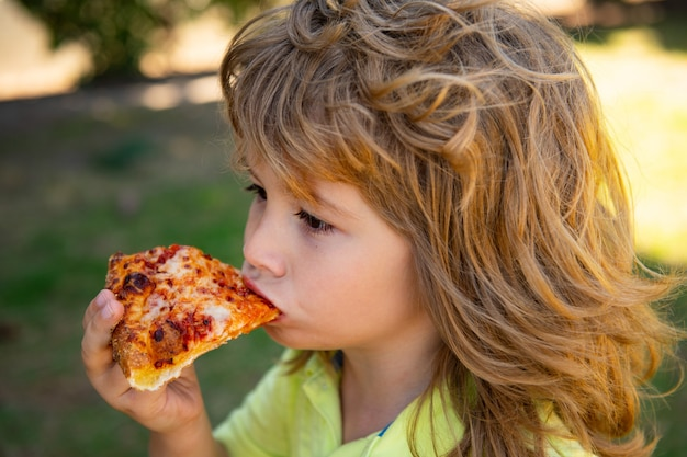 Enfant mangeant un morceau de pizza enfant garçon mange une tranche de pizza au pepperoni les enfants drôles font face à la pizza le meilleur ...