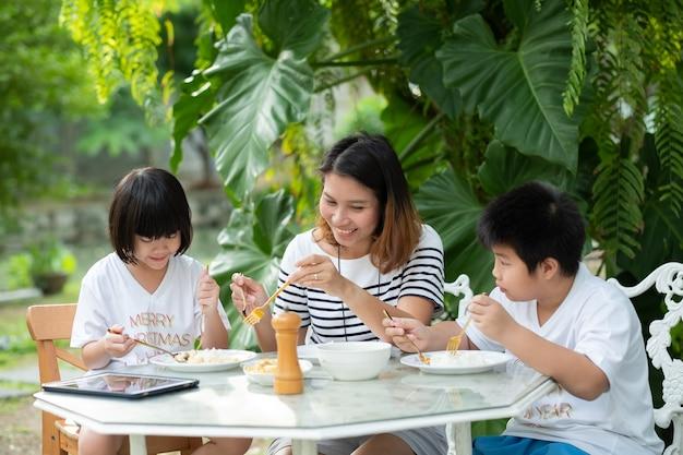 Enfant mangeant de la nourriture avec sa mère, temps heureux, petit-déjeuner