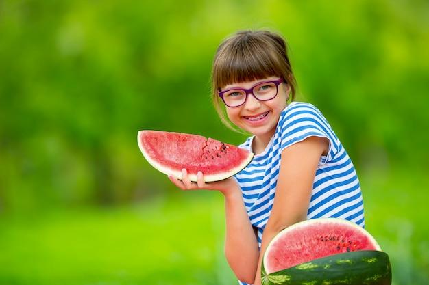 Enfant mangeant de la pastèque pré adolescente dans le jardin tenant une tranche de melon d'eau happy girl kid ea...