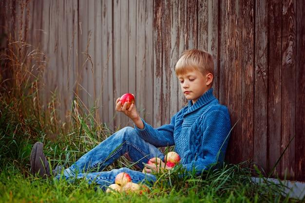 Enfant mangeant une pomme rouge dehors dans le jardin