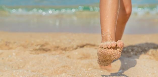Enfant marchant le long de la plage laissant des traces de pas dans le sable