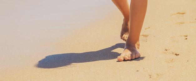 L'enfant marche le long de la plage en laissant des traces de pas dans le sable.