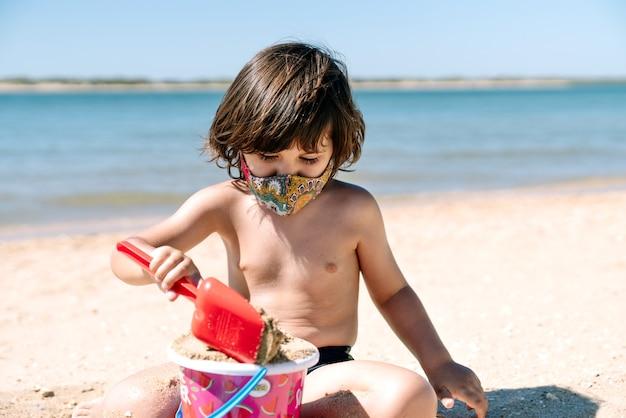 Enfant avec masque facial en vacances à jouer et à profiter de jouets sur le sable d'une plage à côté de l'eau de mer au milieu de la pandémie de coronavirus