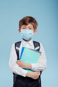 Enfant avec masque médical et sac à dos a des cahiers et des livres à la main isolés sur fond bleu