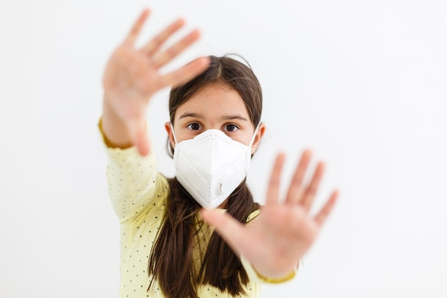 Enfant masqué - protection contre le virus de la grippe. petite fille caucasienne portant un masque pour protéger pm2.5. armes biologiques. bébé sur fond gris avec espace de copie. pandémie épidémique.