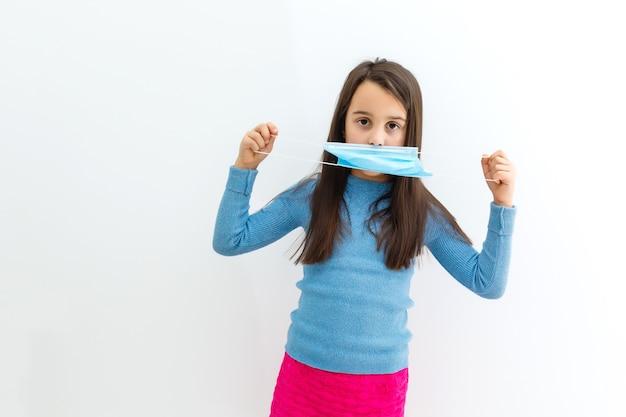 Enfant masqué - protection contre le virus de la grippe. petite fille caucasienne portant un masque pour se protéger
